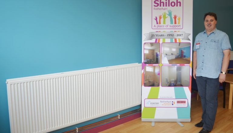 Shiloh Centre Manager Kevin Quinton with one of the Stelrad Elite radiators donated to the centre.