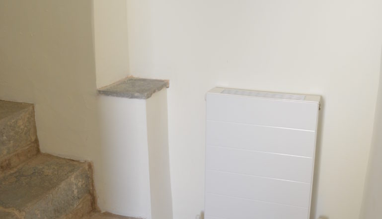 A small Compact with Style radiator at the foot of the original 16th century staircase